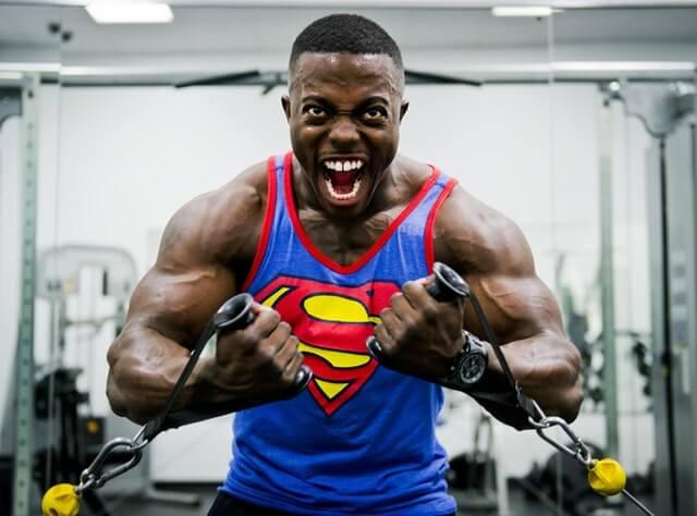 Homme qui fait de la musculation avec un marcel superman